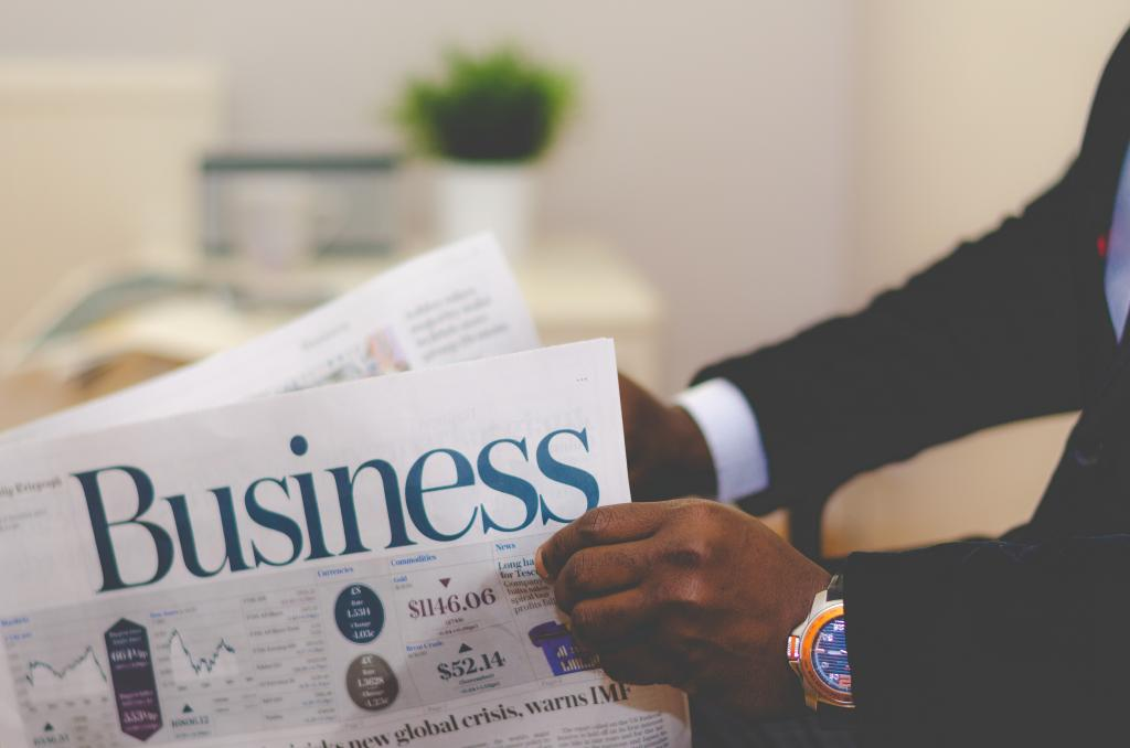 photo of business man holding a business newspaper